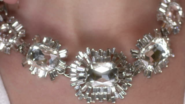 Female hands adjusting necklace around the neck video