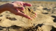 Female hands and falling sand video