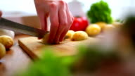 Female hands cutting potatoes on wooden board. video