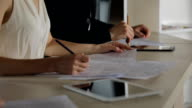 Female hands holding a plan of building, sitting next to man and designs on paper video