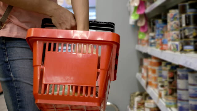 Female hands holding shopping basket and puts goods from the shelves video