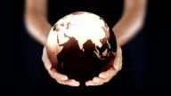Female hands holding the Earth. Starting in Asia. Brown. video