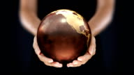 Female hands holding the Earth. Starting in US. Brown. video