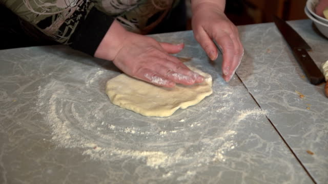 Female hands knead yeast dough for pizza . video