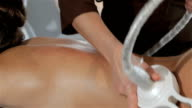 Female hands moves the head of massage machine along the girl's back video