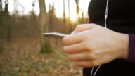 Female hands operanting smart phone in the park. video