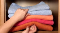 Female hands pulling out of the closet stack of colorful bath towels video