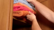 Female hands putting on closet shelf stack of colorful fluffy bath towels video