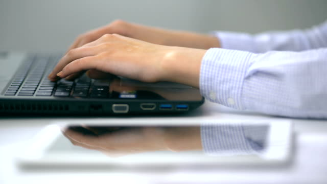 Female hands typing on a laptop keyboard in a white office video