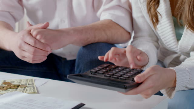 Female hands using calculator, couple planning family budget video