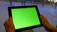 Female hands using tablet pc with green screen in shopping mall. Lot of people skate on indoor ice rink at the background video