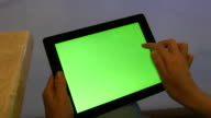 Female hands using tablet pc with green screen in shopping mall. video