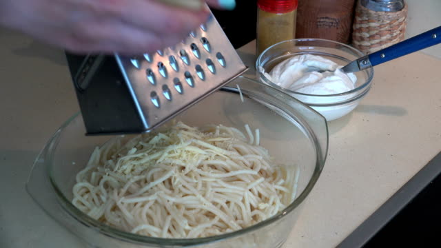 Female hands with shredder grate cheese on spaghetti pasta video
