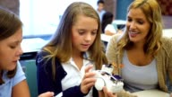 Female high school STEM students examine a robot in technology class video