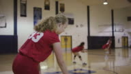 Female high school volleyball player serving a volleyball during a game video