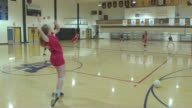 Female high school volleyball players competing in a game video