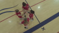 Female high school volleyball players huddled up together in a circle before their match video
