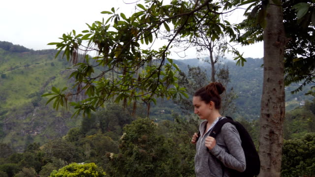 Female hiker going along tropical mount road. Young woman tourist with backpack walking at trail in mountains with beautiful nature landscape at background. Healthy active lifestyle. Travel concept video
