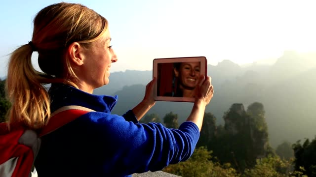 Female hiker on mountain top takes digital tablet picture video