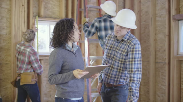 Female homeowner going over building plans on a digital tablet with a general construction contractor video