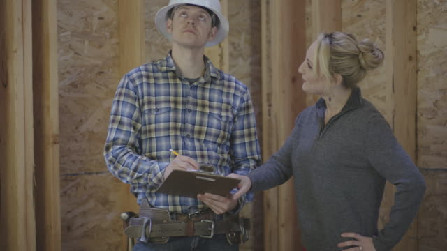 Female homeowner going over building plans with a general construction contractor video