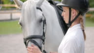 SLO MO Female rider petting white horse on the nose video