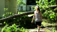Female house owner walk over fallen tree after storm. video