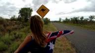 Female in Australia holding flag near kangaroo sign video