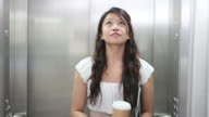 Female in elevator checking hair video