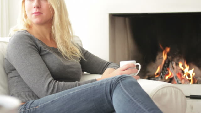 Female in front of fireplace drinking warm tea video