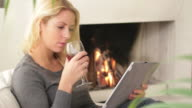Female in front of fireplace looking at digital tablet video
