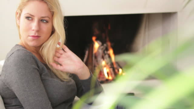 Female in front of fireplace looking to camera video