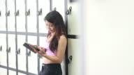 Female in locker room working on digital tablet video