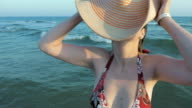 A female in sunglasses putting on her fedora hat video
