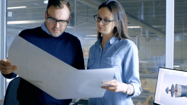 Female Industrial Engineer and Male Chief Engineer Work with Blueprints. CAD Software is Running on Computer and Big Factory is Seen out of the Window. video