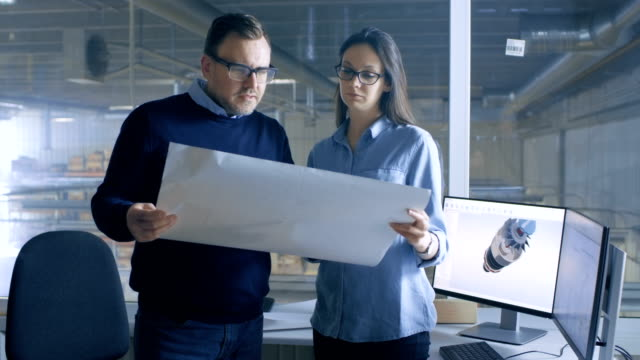 Female Industrial Engineer and Male Chief Engineer Work with Blueprints. Desktop Computer Shows 3D Turbine/ Engine Model. video