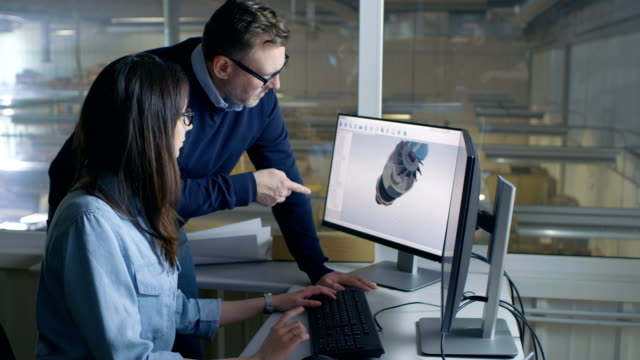 Female Industrial Engineer and Male Project Manager Work on 3D Turbine/ Engine Model in Her CAD Software. Inside of the Factory is Seen From the Office Window. video