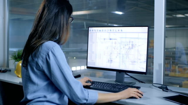 Female Industrial Engineer Working With Technical Blueprints on Her Personal Computer. Inside of the Factory is Seen From Her Office Window. video