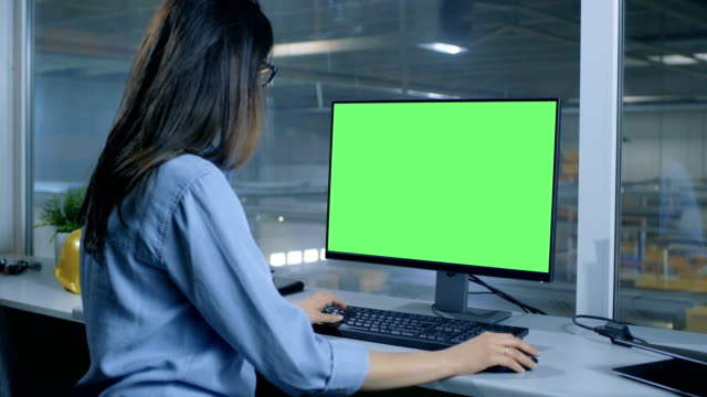 Female Industrial Engineer Works on Her Computer with  Mock-up Green Screen. Inside of the Factory is Seen From Her Office Window. video