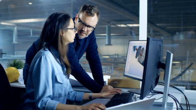 Female Industrial Technician and Male Chief Engineer Designing 3D Turbine/ Engine Model with Help of Cad Software. They Work on a Computer with Two Displays. video
