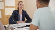 Female insurance agent advising a client at home video