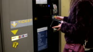 Female is buying a parking ticket on a machine with a credit card video