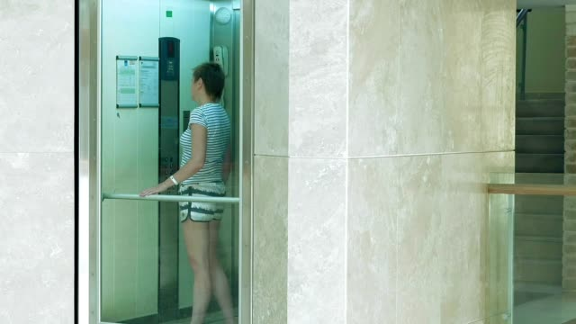 A female is standing in glass moving lift video
