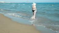 Female is walking towards the sea and in the water video