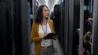 Female IT engineer checking servers in server room using tablet video
