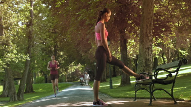 DS Female jogger stretching her legs on the park bench video
