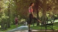 DS Female jogger stretching legs on the park bench video