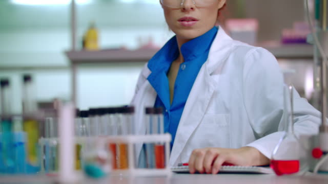 Female lab worker in science laboratory. Lab researcher working with liquid video