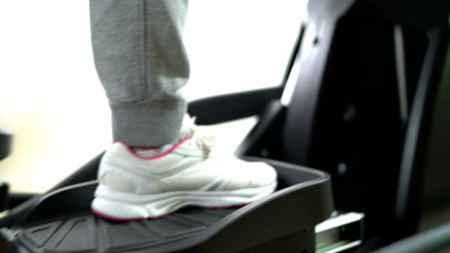 Female legs in sneakers on foot pedals of elliptical trainer while cardio workout video