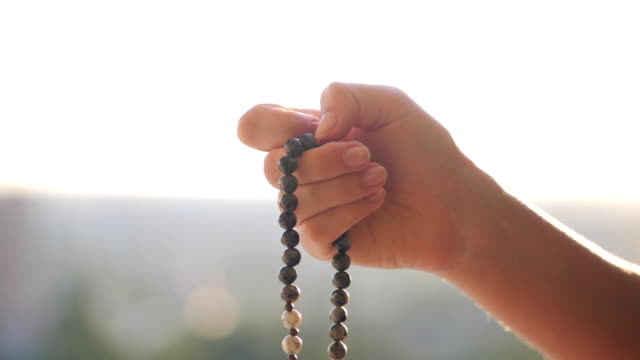 Female lit hand close up on sunset or sunrise, counts Malas strands of gemstones beads used for keeping count during mantra meditations. Woman sits on top above city. Slow motion video